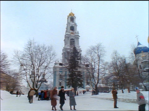 wide shot pan people walking in square in snow / onion domed buildings in background / zagorsk, russia - onion dome stock videos and b-roll footage