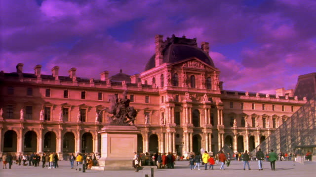 wide shot pan people walking next to the louvre with the glass pyramide / paris, france - louvre stock videos and b-roll footage