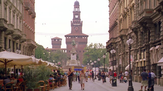 wide shot PAN people walking on street with cafe / church + statue in background / Milan, Italy