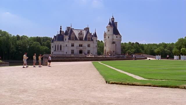 vidéos et rushes de wide shot people walking on the grounds of chateau de chenonceau / france - château