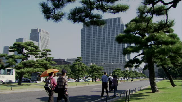 Wide shot people walking through Koyo Gaien plaza in front of Imperial Palace / Tokyo