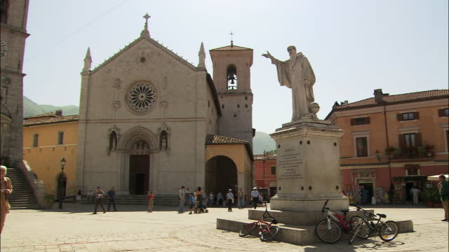 wide shot people walking through san benedetto square with church of st. benedict and statue/ medium shot mature woman walking with guidebook and looking around/ norcia, umbria - ウンブリア州点の映像素材/bロール