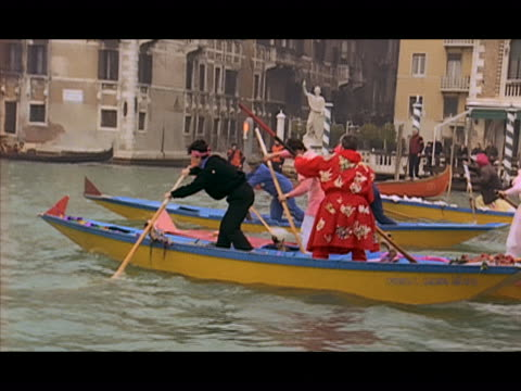 vídeos de stock e filmes b-roll de wide shot people wearing costumes racing gondolas along waterway / pan to team pulling out into the lead / venice, italy - formato letterbox