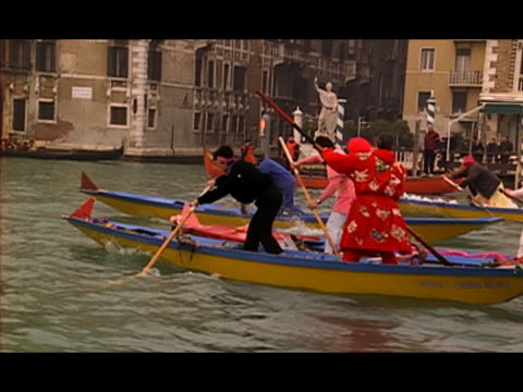 vídeos y material grabado en eventos de stock de wide shot people wearing costumes racing gondolas along waterway / pan to team pulling out into the lead / venice, italy - formato buzón