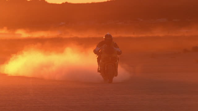 Wide shot person driving and slowing down on motorcycle in desert at dusk / California