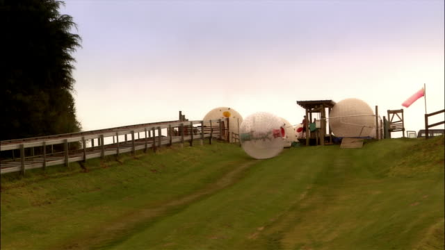 wide shot person in zorb rolling down hill/ selwyn heights, new zealand - moving down stock videos & royalty-free footage