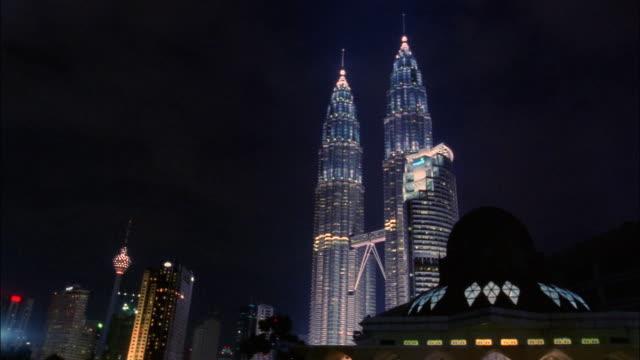 vidéos et rushes de wide shot petronas towers, menara maxis, and al-asyikin mosque at night/ kuala lumpur, malaysia - tour menara kl