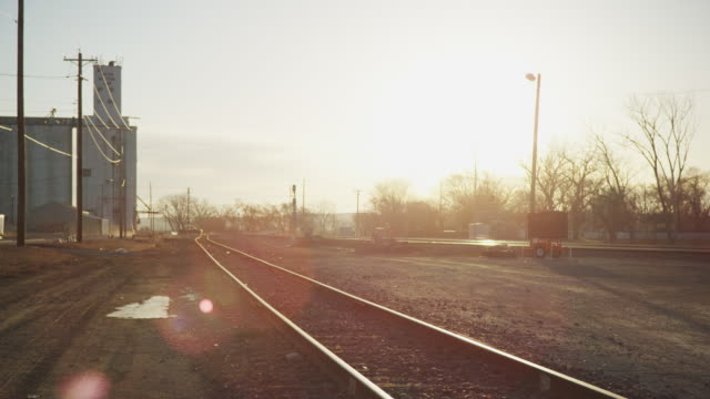 Wide shot - pickup truck drives into freight train yard in the early morning.