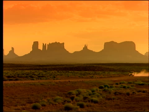 wide shot pickup truck passes on desert road / sil of buttes background / filter - southwest usa stock videos and b-roll footage
