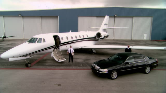 Wide shot Pilot and chauffeur standing near private jet and luxury car at Opa Locka Airport/ Miami, Florida, USA