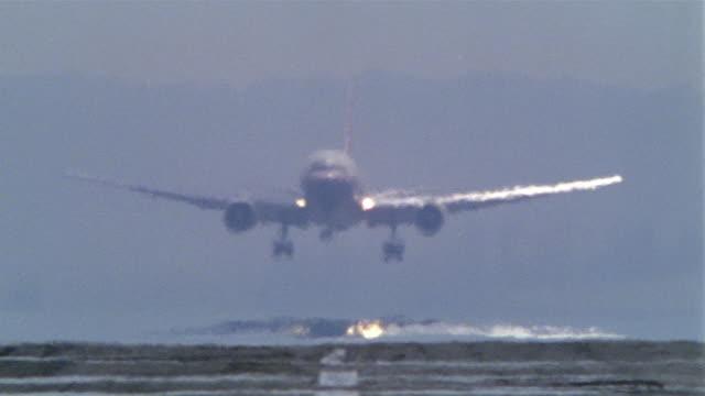 wide shot plane landing on runway behind heat wave distortion - wide shot stock videos & royalty-free footage