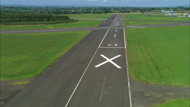 Wide shot plane point of view landing on runway at Carlisle Airport / Cumbria, England