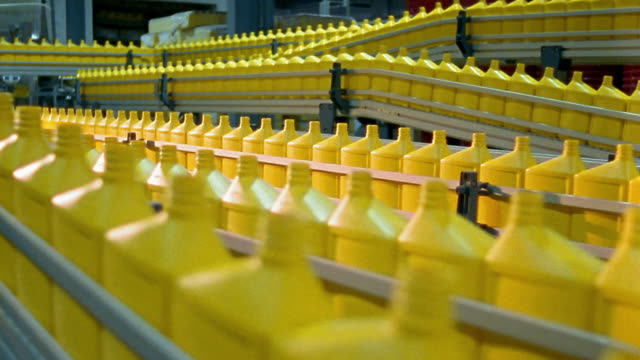 wide shot plastic yellow motor oil bottles moving on conveyor belts - flasche stock-videos und b-roll-filmmaterial