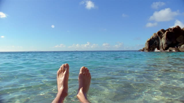 Wide shot point of view feet floating in water with blue sky in background / St Barthelemy, French West Indies