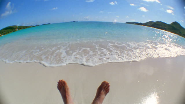 Wide shot point of view feet on beach as tide rolls in / tilt up airplane in sky / St Barthelemy, French West Indies
