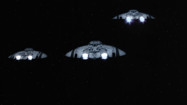 wide shot point of view firing at three spaceships and hitting middle ship in dogfight / middle ship exploding - 宇宙船点の映像素材/bロール