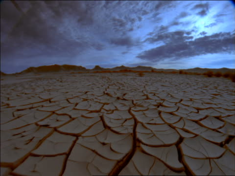 wide shot point of view + PAN over cracked earth with time lapse storm clouds above / Death Valley, Mojave Desert, California