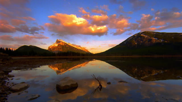 wide shot point of view over mountain lake / time lapse pink clouds in sky + reflected in lake / Banff National Park, Canada
