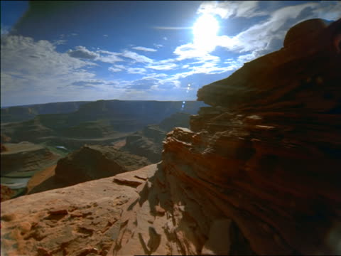 wide shot point of view past rock formations toward canyon with time lapse clouds above / Grand Canyon, Arizona
