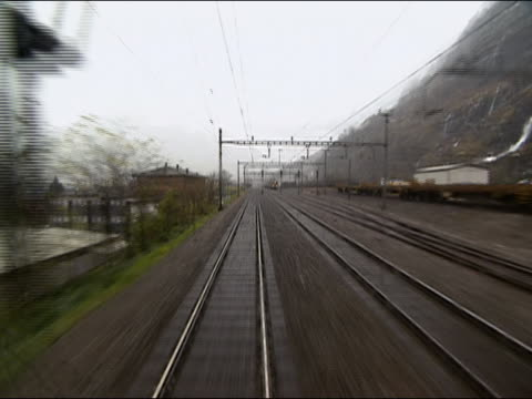 2002 Wide shot point of view train on moving along mountainside and passing railway station