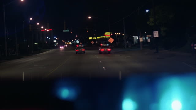 wide shot police car point of view driving behind police cars with flashing lights at night/ rack focus flashing lights/ miami - crime stock videos & royalty-free footage