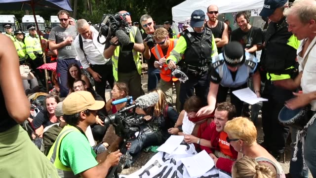 wide shot, police officers giving out notices to protestors. protesters gather outside a drill site operated by cuadrilla resources ltd on august 19,... - west sussex stock videos & royalty-free footage