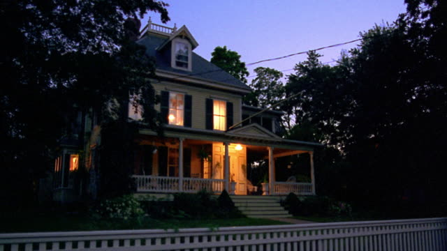 vidéos et rushes de wide shot porch + house lights turning off in suburban house with fence at dusk - plan de situation