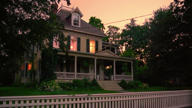 wide shot porch + house lights turning off + on in suburban house with fence at dusk