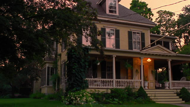 wide shot pan porch + house lights turning on in suburban house at dusk - dusk stock videos & royalty-free footage