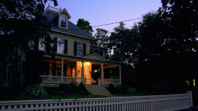wide shot PAN porch + house lights turning on in suburban house at dusk
