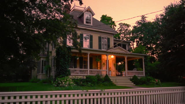 wide shot porch + house lights turning on in suburban house with fence at dusk