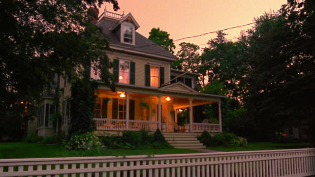 wide shot porch + house lights turning on + off in suburban house with fence at dusk