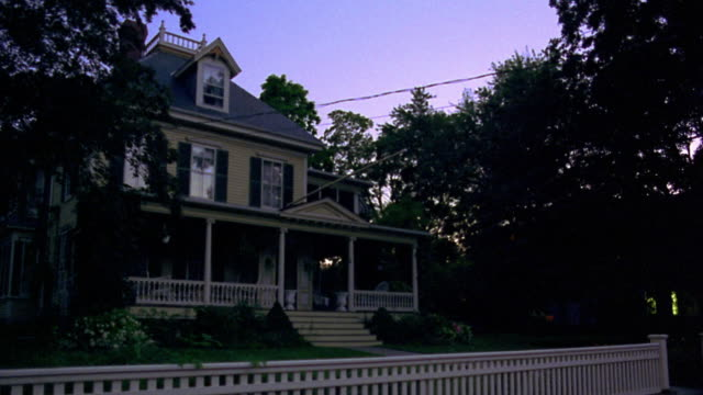 wide shot PAN porch light turning on in suburban house with fence at dusk