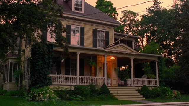 wide shot porch light turning on + off in suburban house at dusk
