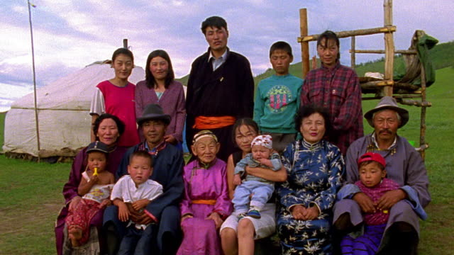 vídeos de stock e filmes b-roll de wide shot portrait large asian family sitting + standing outdoors with ger in background / mongolia - asiático e indiano