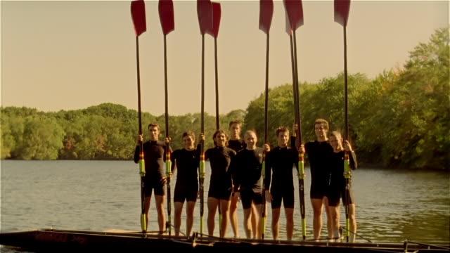 wide shot portrait of crew team standing on pier holding oars / tilt down to river / tilt up men making number 1 signs - number 1 stock videos & royalty-free footage
