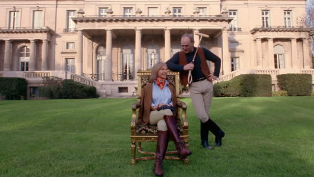 vidéos et rushes de wide shot portrait of female equestrian sitting on gilded chair and male polo player in front of mansion - stéréotype de la classe supérieure