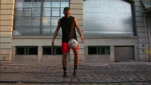 Wide shot portrait of man playing with soccer ball on city street / looking at camera / Dumbo, Brooklyn, New York