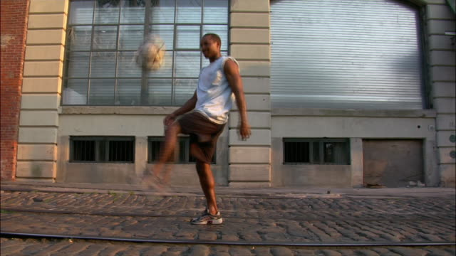 vídeos y material grabado en eventos de stock de wide shot portrait of man playing with soccer ball on city street / catching it on his back and smiling at camera / dumbo, brooklyn, new york - patadas