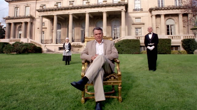 wide shot portrait of man sitting on gilded chair with servants standing at attention in front of mansion - prosperity stock videos & royalty-free footage