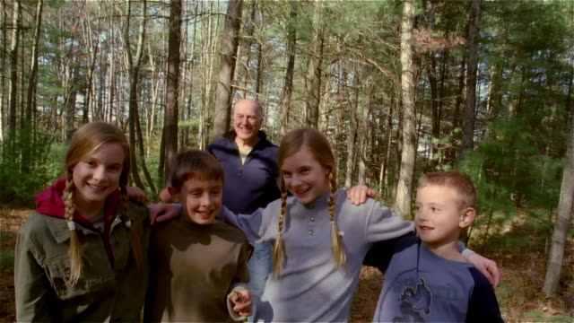 wide shot portrait of two boys and twin girls in the woods with their arms around each other / grandfather coming up behind them and joining hug - familie mit mehreren generationen stock-videos und b-roll-filmmaterial