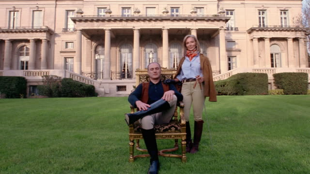 Wide shot portrait of wealthy couple in equestrian clothing in front of mansion (man sitting on chair)