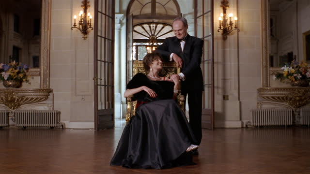 Wide shot portrait of wealthy couple in formal attire in foyer of mansion (woman sitting in gilded chair)