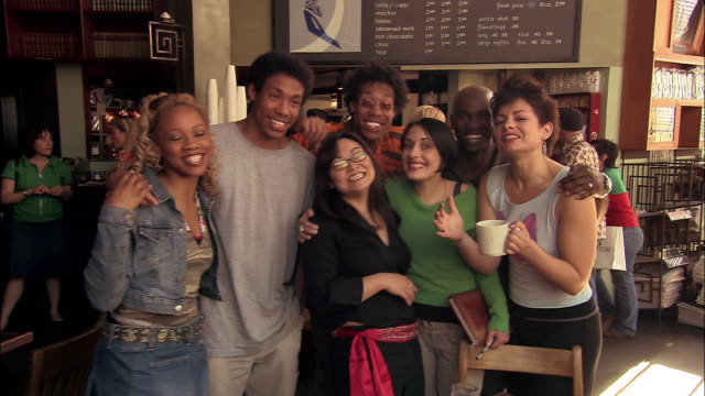 wide shot portrait of young people in coffeehouse smiling at cam / seattle - organised group photo stock videos & royalty-free footage
