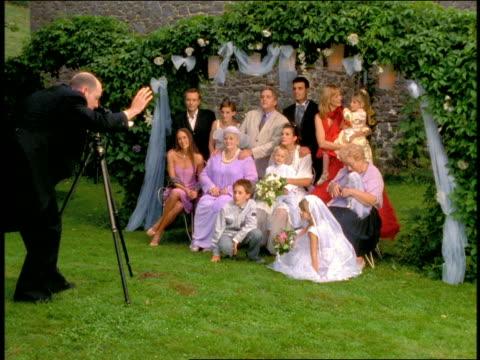 vidéos et rushes de wide shot portrait photographer taking picture of bride + groom posing with family  outdoors - photographe