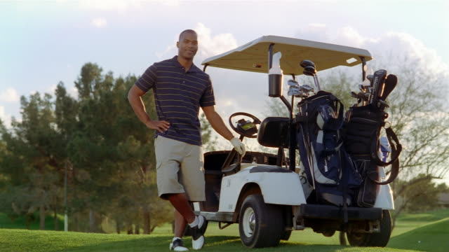 vídeos y material grabado en eventos de stock de wide shot potrait man posing next to golf cart on golf course - zapato de golf