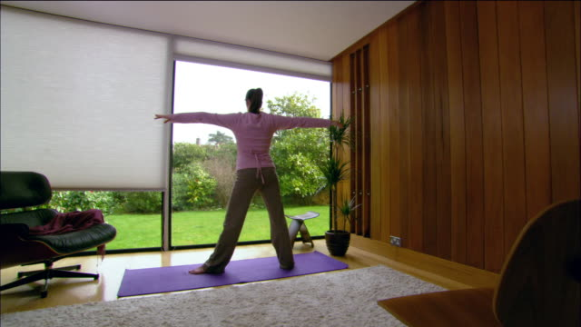 wide shot pregnant woman practicing yoga at home / east grinstead, england - viewpoint stock videos and b-roll footage