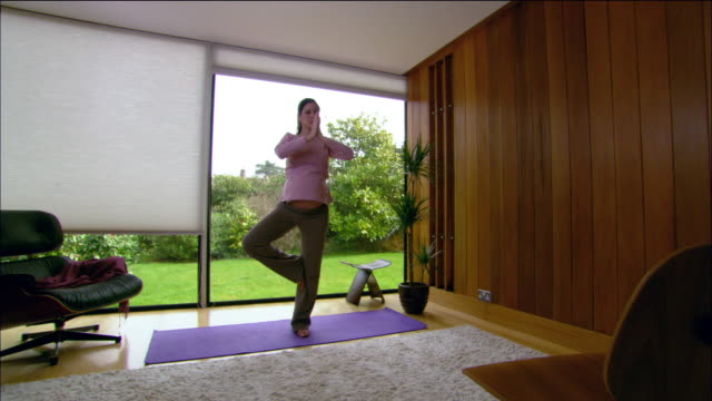 Wide shot pregnant woman practicing yoga at home / East Grinstead, England