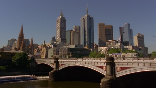 Wide shot Princes Bridge over Yarra River with skyscrapers in background/ Melbourne, Australia