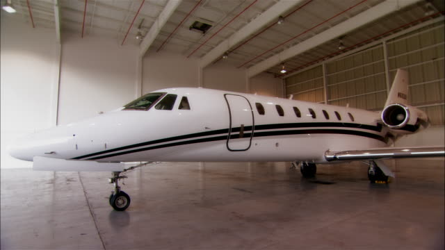 wide shot private jet in hangar at opa locka airport/ miami, florida, usa - 飛行機格納庫点の映像素材/bロール